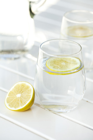 lemon water: Glass of water with lemon on white background Stock Photo