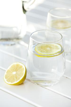 vaso con agua: Vaso de agua con limón en el fondo blanco Foto de archivo