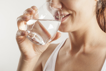bodies of water: Young woman drinking  glass of water