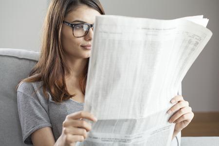 Jonge vrouw krant lezen Stockfoto