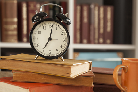 o'clock: Pile of books with oclock on desk Stock Photo