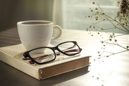 Cup of coffe on reading book with glasses on table