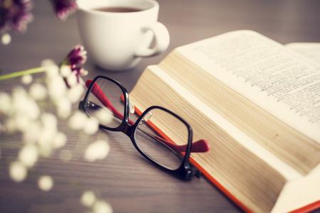 personas leyendo: La lectura del libro con gafas en la mesa de madera