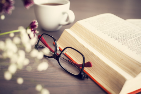 person reading: Reading book with eyeglasses on wooden table