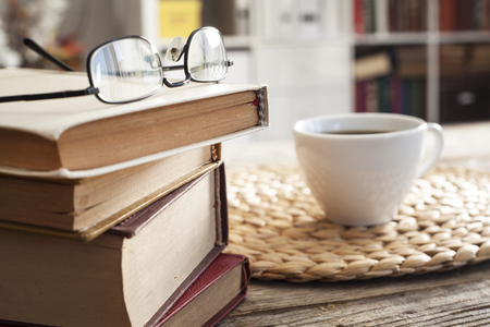 Pile of books with reading glasses on desk