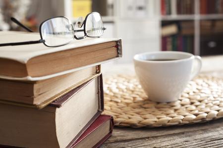 Stapel van boeken met een leesbril op het bureau