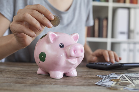 coin bank: Putting coin in piggy bank