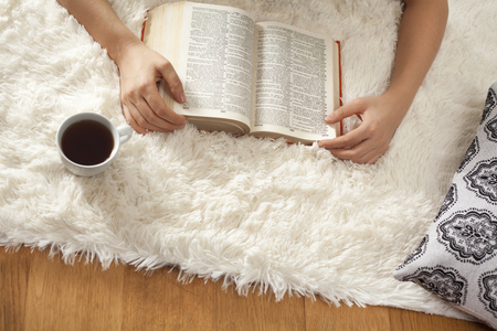 Young woman reading book on carpet