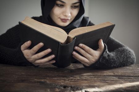 Muslim woman reading holy islamic book koran
