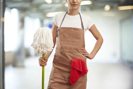 Jonge vrouw met schoonmaakartikelen in het gebouw