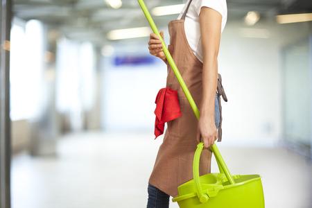 Frau mit Reinigungsmittel im Gebäude