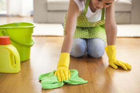 가정에서 바닥을 청소하는 천을 가진 여자