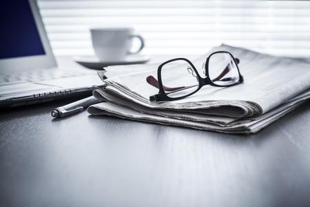 Krant en computer op tafel