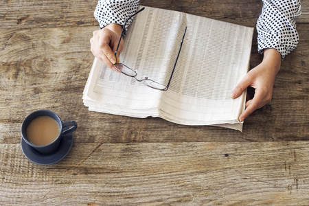 broadsheet: Reading newspaper on wooden table