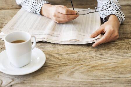 broadsheet newspaper: Reading newspaper on wooden table