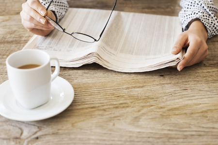 Reading newspaper on wooden table