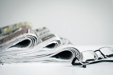Newspapers with eyeglasses on white background Stock Photo