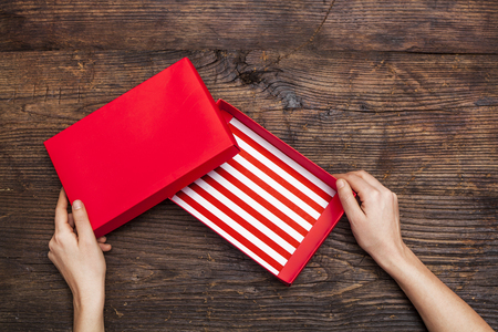 box: Woman hands holding empty gift box on wooden background