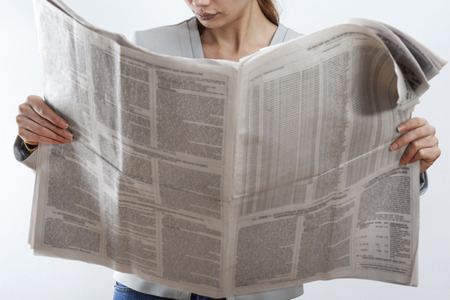 Woman reading newspaper on white background Standard-Bild