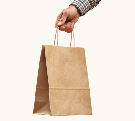Man holding paper shopping bag on gray background