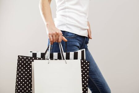 paper bag: Woman holding paper shopping bags on gray background