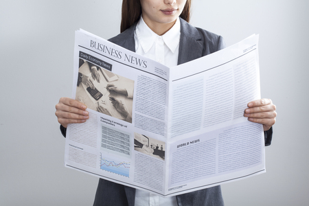 woman looking: Businesswoman reading newspaper on gray background Stock Photo