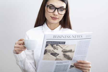 Businesswoman reading newspaper on gray background Stock Photo