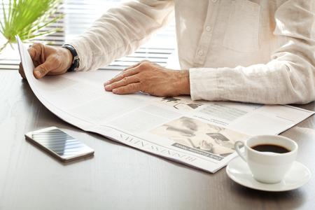 Hombre leyendo el periódico en la mesa Foto de archivo - 70995432