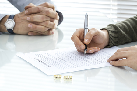 Wife signs divorce decree form with ring Stockfoto
