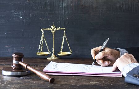Man ondertekening document met hamer en rechtvaardigheid schaal