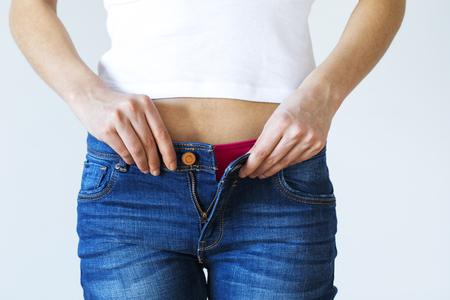체중 증가의 여자가 청바지를 입고 옷 입어요 스톡 콘텐츠