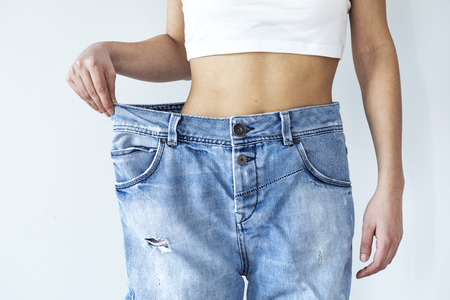 Weight loss woman with old jean on gray background Reklamní fotografie
