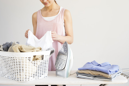 Young woman ironing clothes on ironing board 스톡 콘텐츠