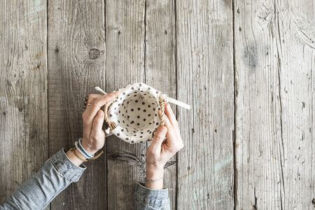 wooden basket: Woman hands holding basket on wooden table