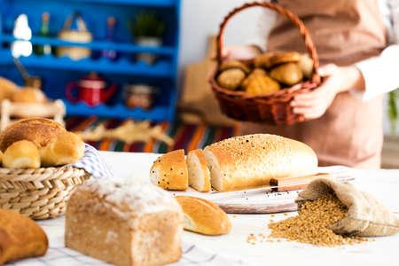 Female hands holding freshly bread in basket Stock Photo