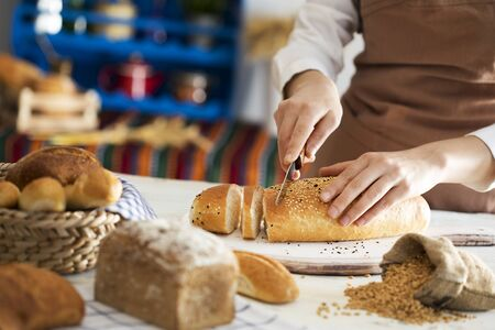 Female hands cutting freshly bread Stock Photo