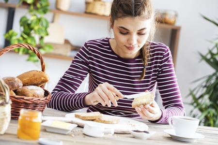 버터 빵을 먹는 젊은 여성