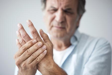 Oude man met vingerpijn Stockfoto