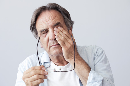 Old man with eye fatigue Stock Photo