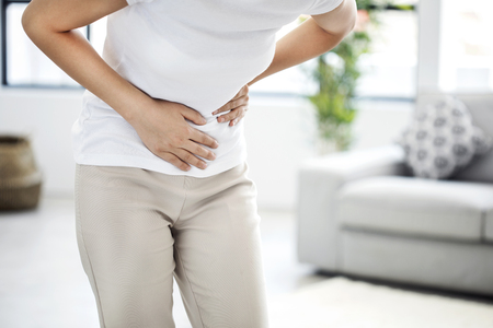 Young woman with stomach pain 스톡 콘텐츠