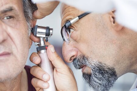 Doctor holding otoscope and examining ear of senior man Stock Photo