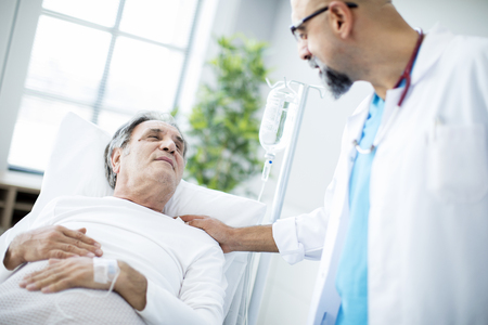 Doctor talking to patient in hospital bed Stockfoto