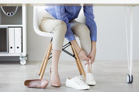 La mujer de negocios joven cambia sus zapatos debido a la fatiga