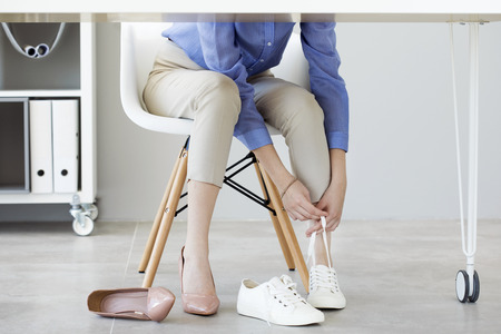 Young business woman changes her shoes due to fatigue