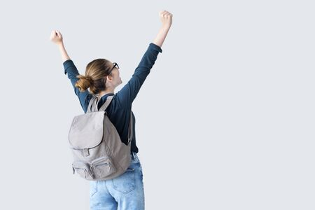 Happy student with arms raised on air Stock Photo