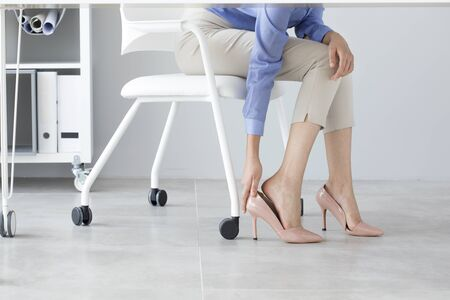 Young woman suffering from foot pain in office