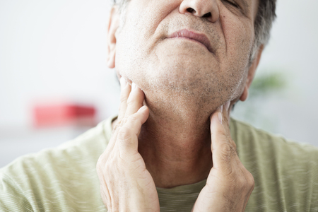 Old man feeling painful in the throat