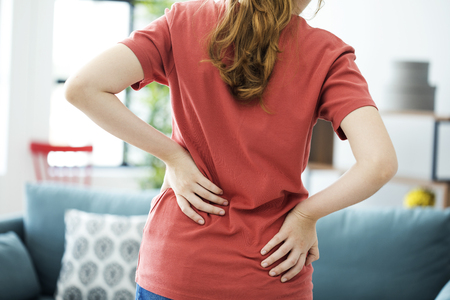 Young woman with back pain 스톡 콘텐츠
