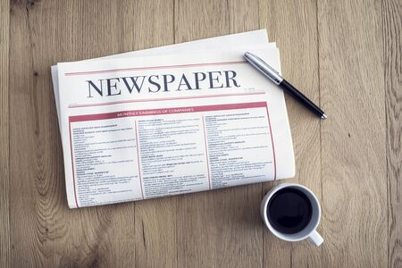 Reading newspaper and drinking coffee on wooden background Archivio Fotografico