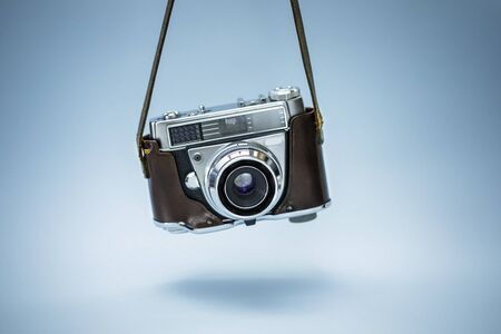 Hanging  realistic photo camera over blue background Banco de Imagens